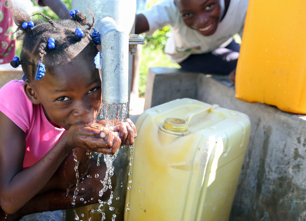 On its 36th anniversary of serving the poor, Food For The Poor thanks its donors for what they have done for the destitute in 17 countries in the Caribbean and Latin America. Food For The Poor has installed a total of 2,064 water wells. This little girl in Haiti is happy to have clean, fresh water from a Food For The Poor water well to drink. (Photo by Food For The Poor)