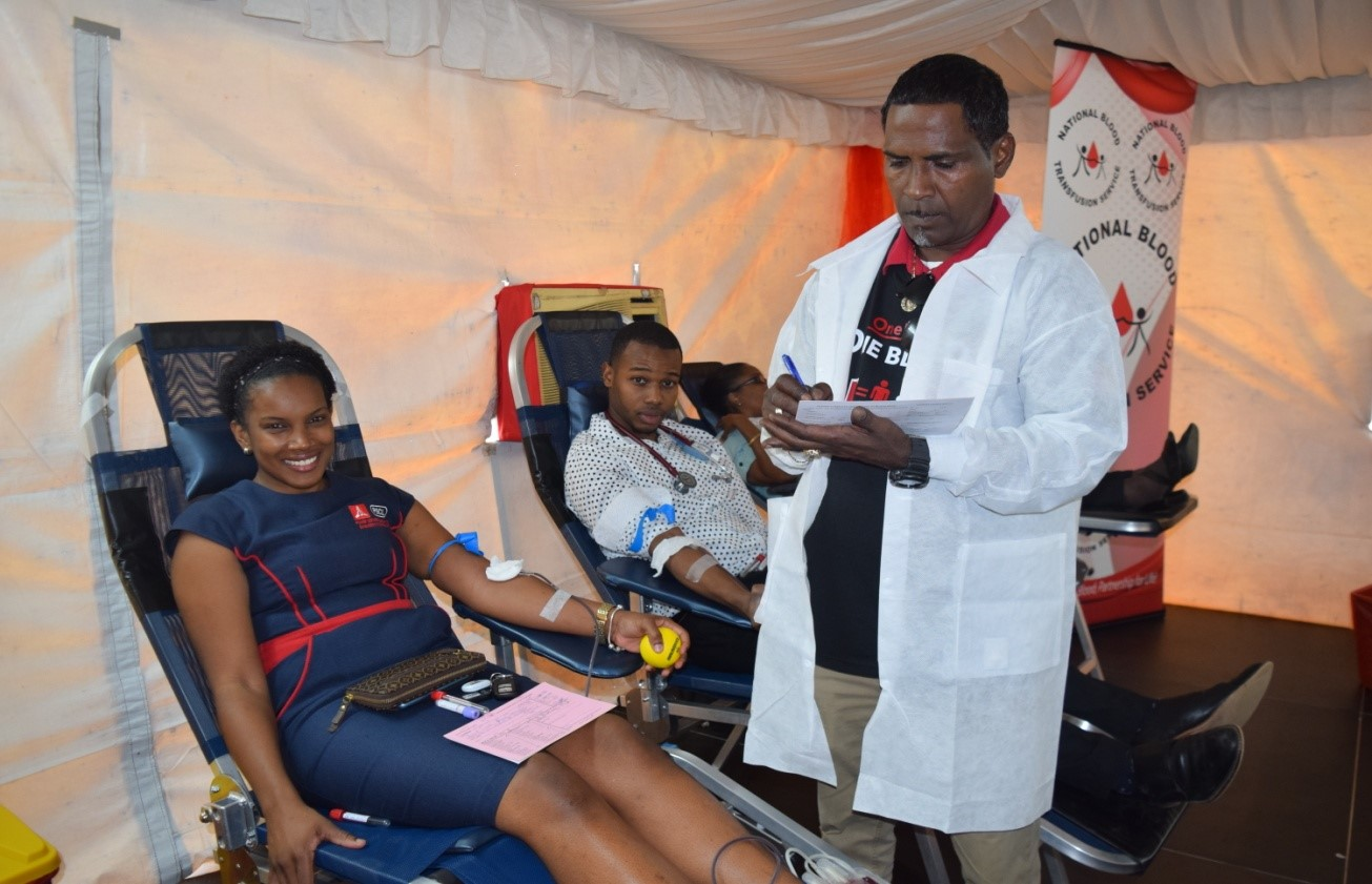 Technical Assistant and Phlebotomist at the National Blood Transfusion Service, Christopher Copeland (standing) assists Project Manager at the Power Services Company Ltd. Lisselle Bennett (left) and Medical Officer from the Mandeville Regional Hospital, Dr. Kharl Watkis in making their donation at the 'One Love, One Blood' donation drive